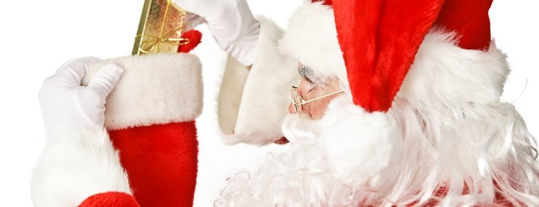 Santa Clause putting a shiny Christmas present into a stocking