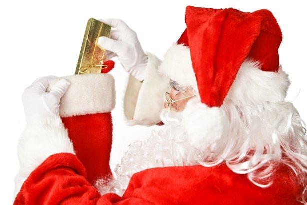 Santa Clause putting a shiny Christmas present into a stocking