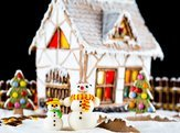 decorative snowmen and gingerbread house with lights inside