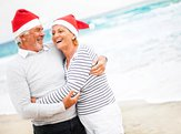 Senior couple at the beach hugging and laughing wearing Santa hats