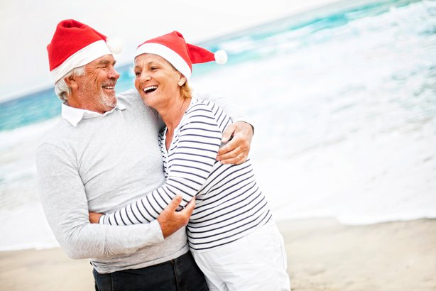 Senior couple at the beach hugging and laughing wearing Santa hats