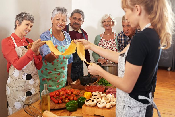 Group of older people making pasta in a cooking class