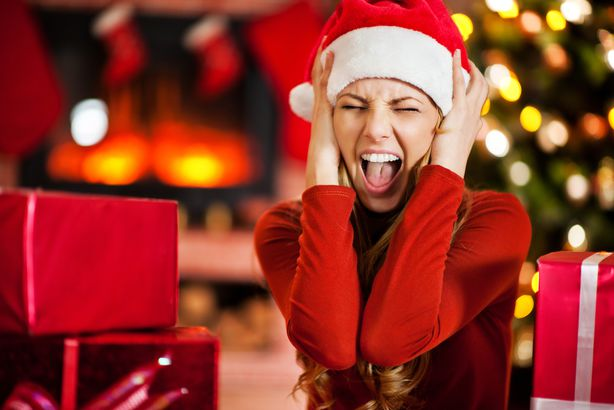 young woman wearing Santa's hat is screaming