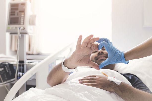 patient in hospital bed making heart shape with doctor