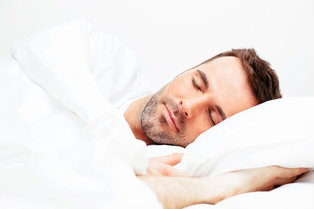 man sleeping in white bedding