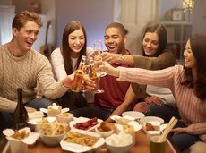 Group of friends toasting drinks and having takeout at home