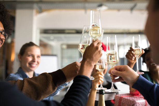 group of people toasting sparking wine during the holidays