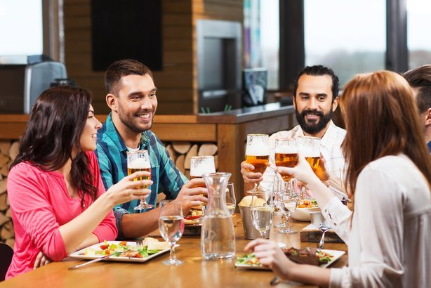 smiling friends having dinner and drinking beer at restaurant