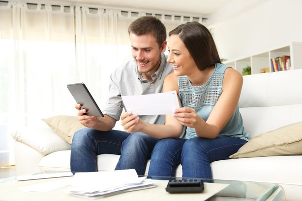 young couple budgeting sitting on a couch in the living room at home