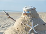 snowman on the beach with shells as mouth and sun glasses