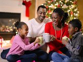 Family sitting at home during Christmas with mugs of cocoa