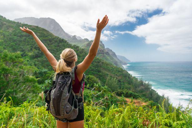 hiker with hands up in Kauai, Hawaii