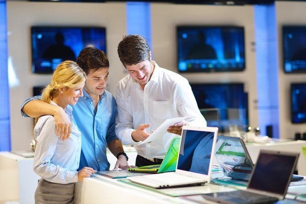young couple in consumer electronics store looking at laptops