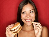 woman eating burger and fries smiling on red background