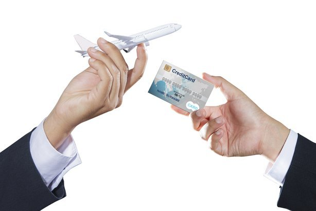 airplane and credit card on businessman hand