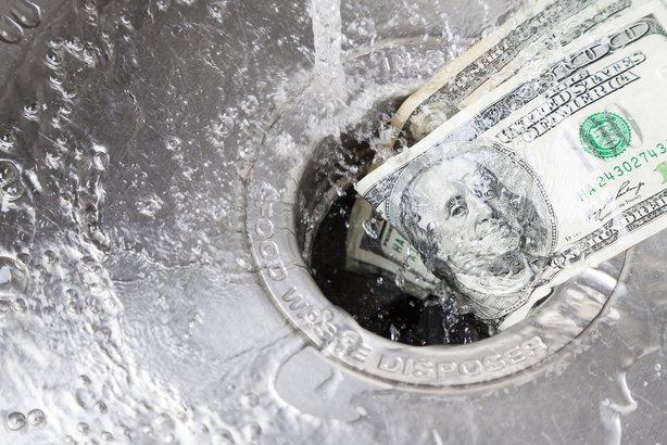hundred dollar bills going down the drain