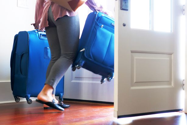 woman carrying luggage out front door of home