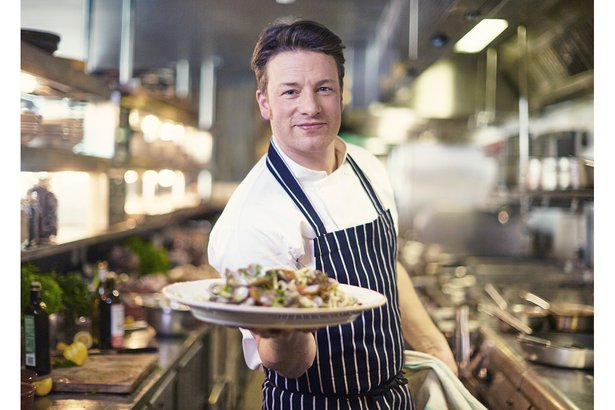 Jamie Oliver holding up plate of food in restaurant kitchen