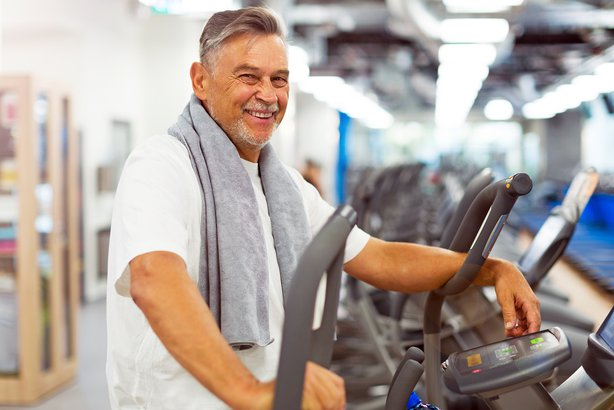 Older man at the gym with a towel around his neck