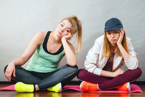 Two girls looking depressed and lazy in their workout clothes