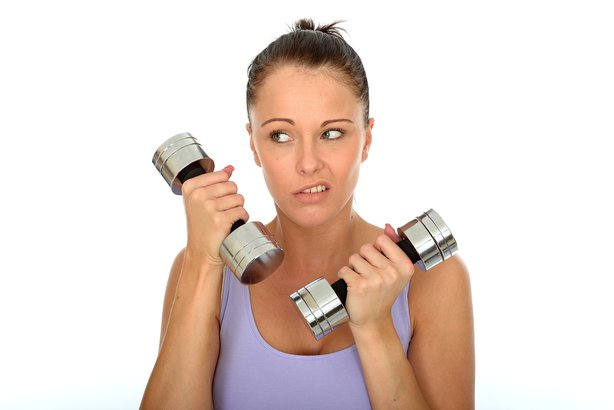 Unhappy woman holding weights