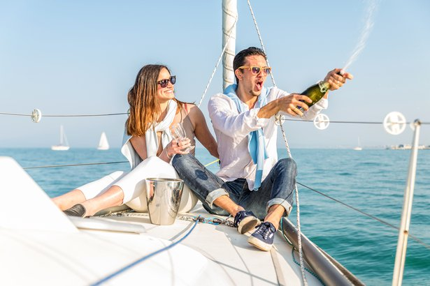 two young adults drinking champagne and having fun on a boat