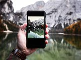 Closeup of smart phone taking picture of mountains and lake