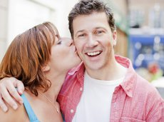 Happy man getting a kiss on the cheek from his wife
