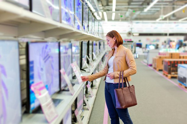 Woman shopping in an electronics store and looking at tvs