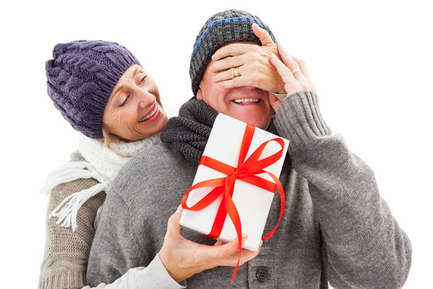 Senior or mature woman handing present to her husband with his eyes closed