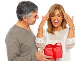 Woman surprised and happy opening a red present from her husband