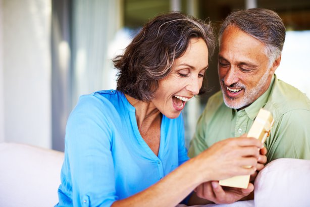Happy mature woman opening a gift from her husband