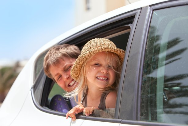 two happy kids hanging out of car window
