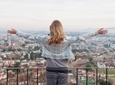 traveler woman with flying hair and raising hands looks at the landscape of Cholula, Mexico