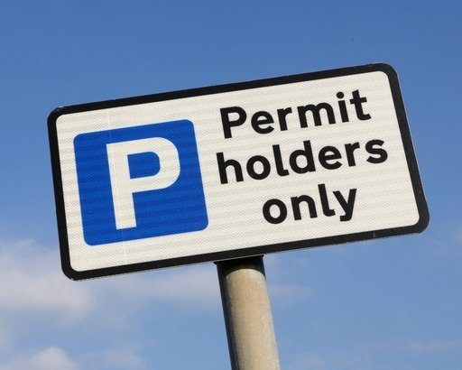 permit holders car parking sign against a partly cloudy sky