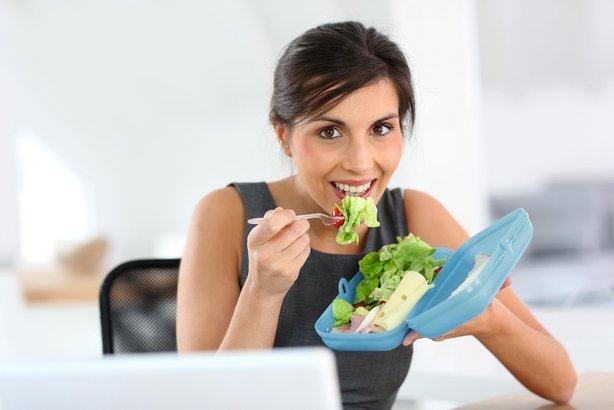 woman eating salad lunch at work