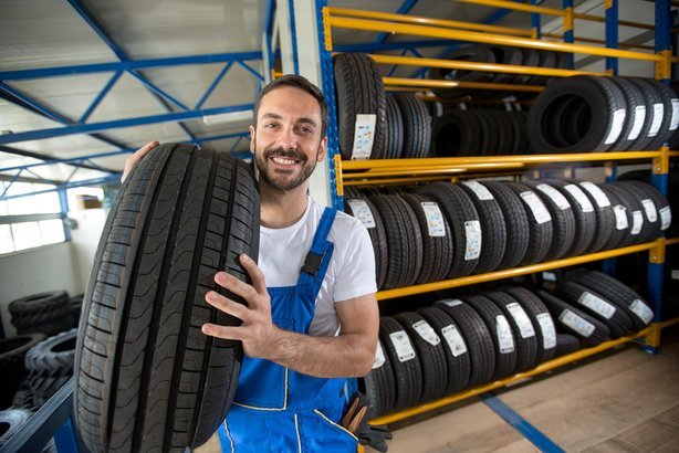 guy with tire in auto store