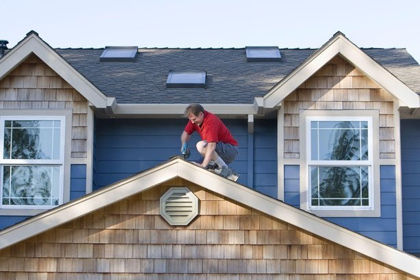 man working with a drill on a roof
