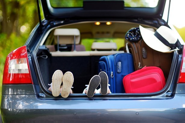 two sets of kids' feet in a car of trunk during vacation