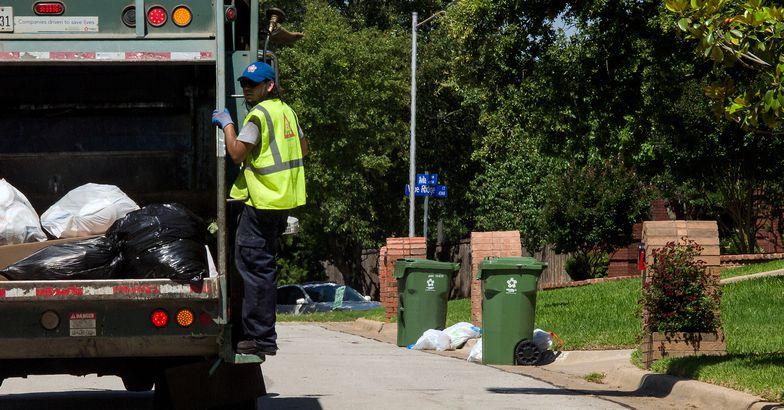 garbage truck with sanitation worker in suburbian neighborhood