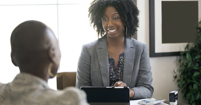 businesswoman in an office with a client giving legal advice about taxes