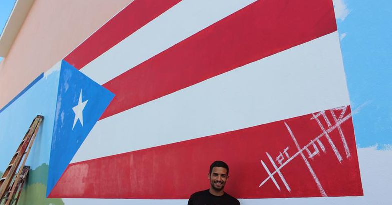 héctor collazo hernández holding paint brush standing in front of flag mural
