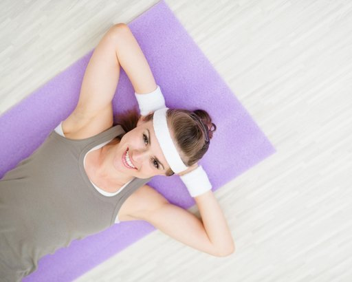 smiling fitness woman laying on fitness mat