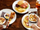 two phones taking pictures of food on table