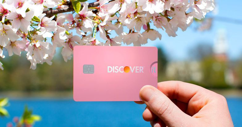 hand holding pink discover it card with pink flowers and lake in background
