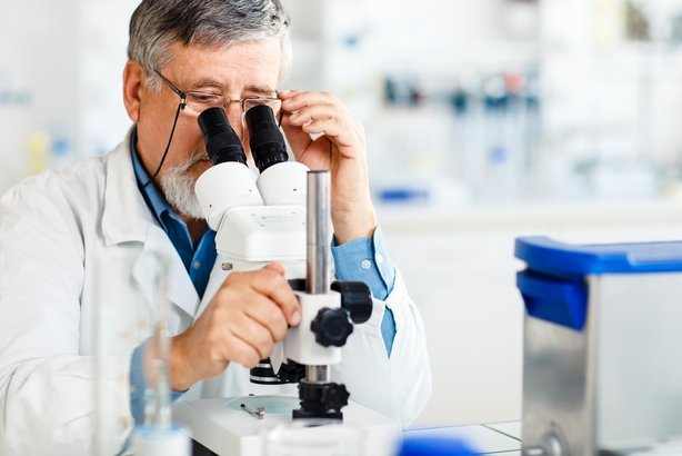 senior male researcher carrying out scientific research in a lab using a microscope