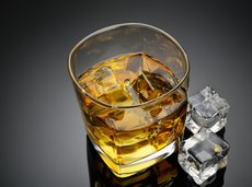 whiskey in glass with ice cubes on table