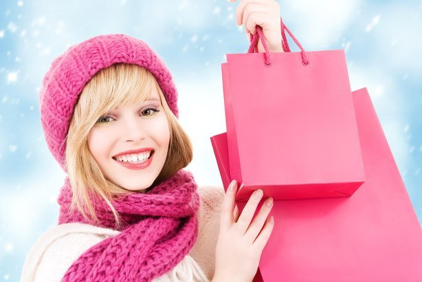 happy woman in hat with pink shopping bags