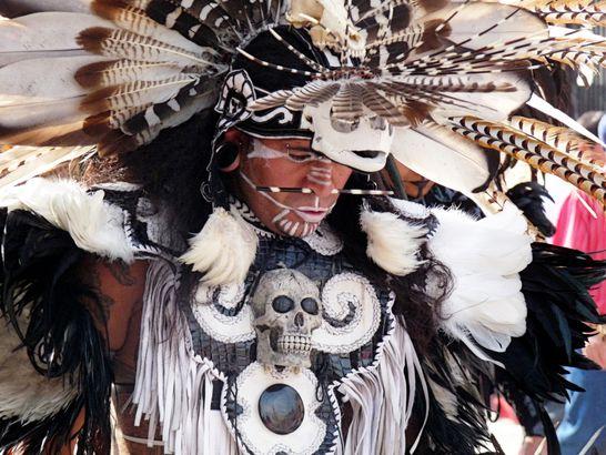 Man wearing elaborate head dress of feathers and skulls to celebrate Dia de Meurto