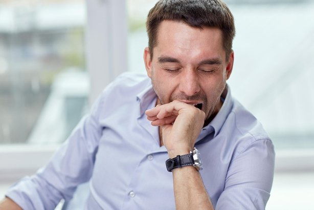yawning tired man at home or office